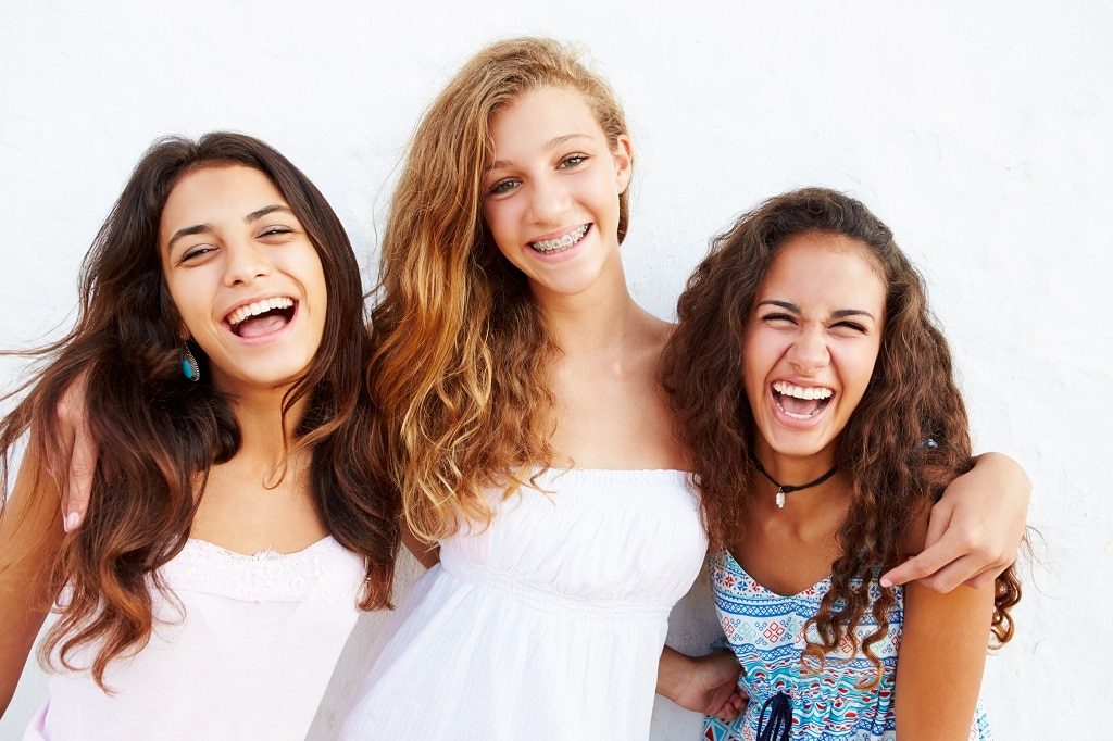 Is Invisalign Teen Right for Me? Image shows three teen girls smiling, one with traditional braces